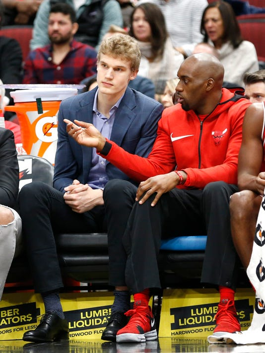 Chicago Bulls' Lauri Markkanen, left, listens to Quincy Pondexter on the bench during the first half of an NBA basketball game against the Boston Celtics, Monday, Dec. 11, 2017, in Chicago. (AP Photo/Charles Rex Arbogast)