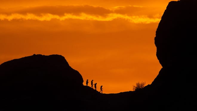 Hikers climb the Papago Buttes at sunset on Sunday, June 26, 2016, as pictured from Hole-in-the-Rock in Phoenix.