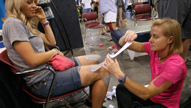Paige Corlet tapes St. George Marathon participant Camie Polster's knees at the Advanced Health and Pain Center's booth at the St. George Marathon Expo on Oct. 3, 2014 at the Dixie Convention Center.