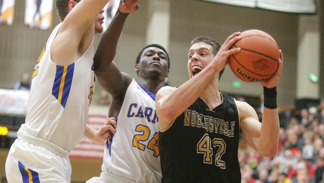 Noblesville's John Kiser (42) snatches a rebound from Carmel's Garrett Covington (24) and Trenton Richardson on March 2, 2016, in Indiana High School Athletic Association first-round sectional action at Noblesville.