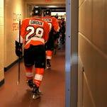 Flyers forwards Claude Giroux and Brayden Schenn head toward the locker room following a loss to the Stars on Tuesday.