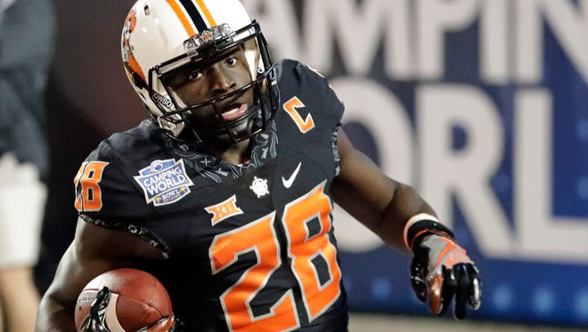 Oklahoma State wide receiver James Washington (28) runs in the end zone completing a 65-yard touchdown pass play against Virginia Tech during the second half of the Camping World Bowl NCAA college football game, Thursday, Dec. 28, 2017, in Orlando, Fla. Oklahoma State won 30-21.