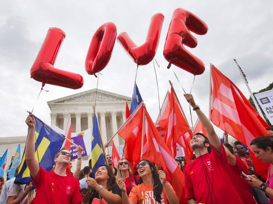 "Same-sex marriage supporters hold up balloons that spell the word ""love"" as they wait outside of the Supreme Court in Washington, Friday June 26, 2015, before the court declared that same-sex couples have a right to marry anywhere in the U.S."