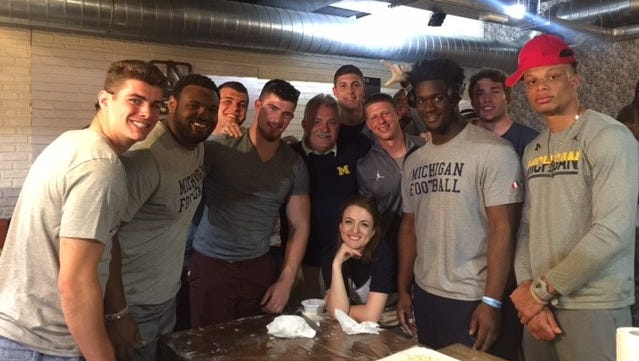 Michigan defensive coordinator Don Brown, center, declared his team the winner of the cooking challenge.