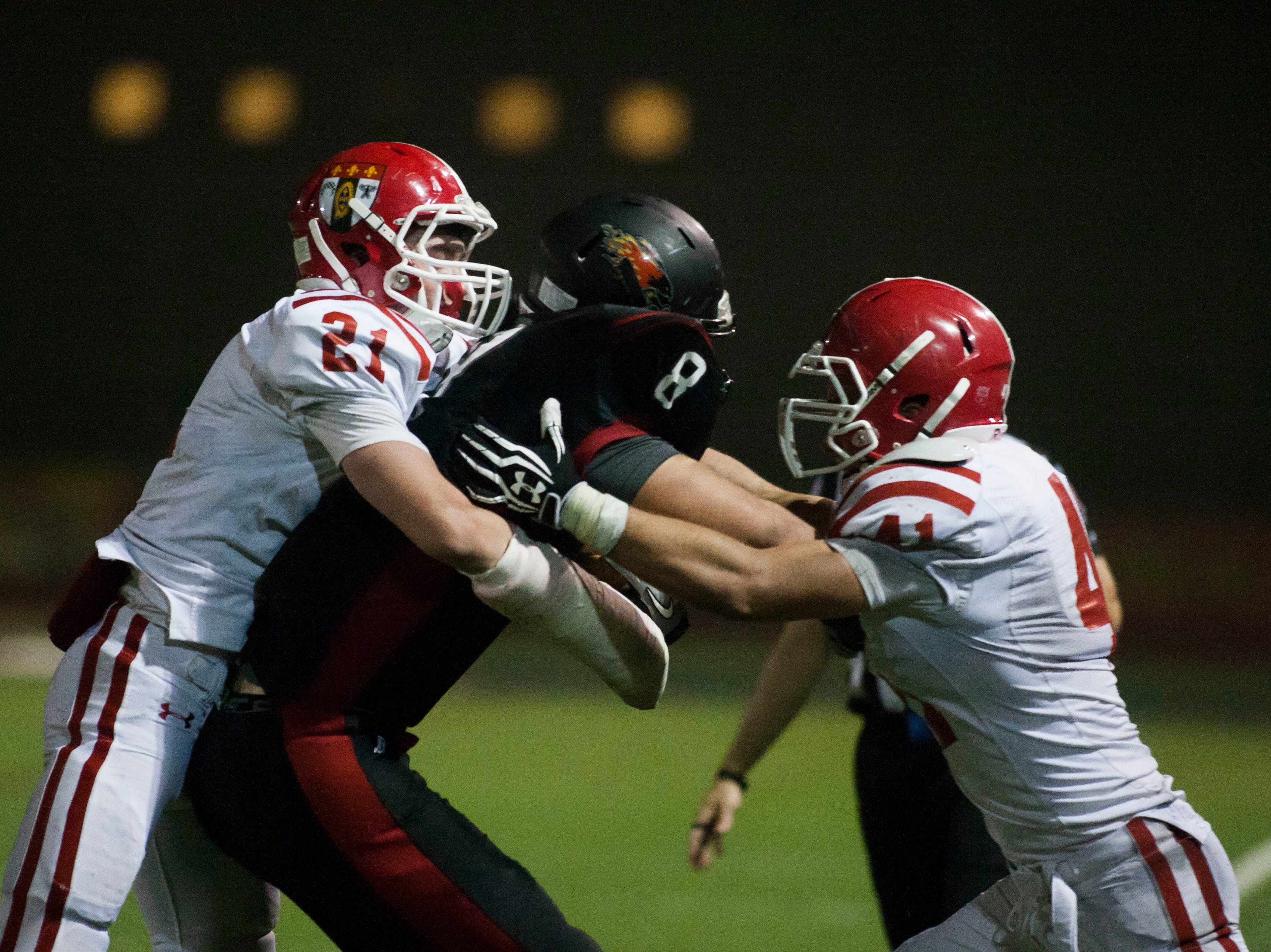 Brophy linebackers Owen Rogers (left) and Walker Adams attempt to tackle Chaparral tight end Trevor Wood during the Brophy College Prep and Chaparral football game at Chaparral High School on Thursday, October 17, 2013 in Scottsdale.