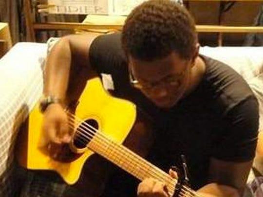 Joseph Elone plays guitar.