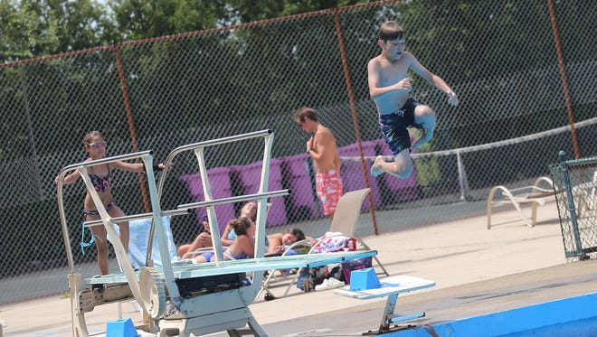 Children makes use of the diving board at the Woodland Club pool on Tuesday.