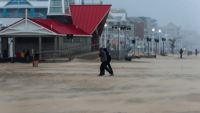 A couple races off the beach to avoid sand and rain on Friday afternoon in Ocean City.