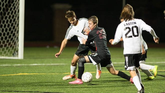 Bennett's Charlie Kerrigan (22) moves the ball past Easton's defenders.
