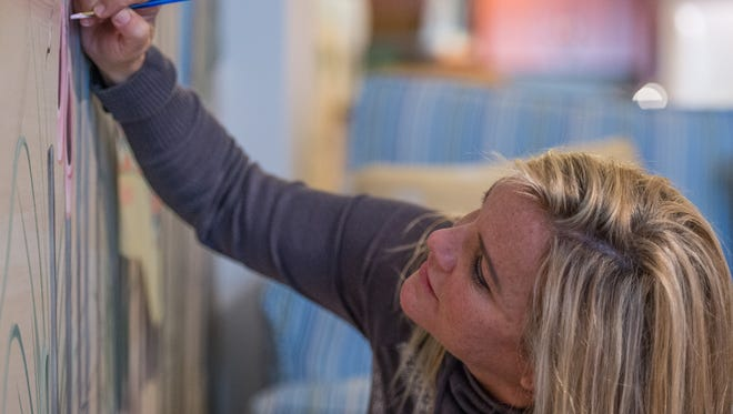 Pam Mason, of Berlin, adds names to a completed mural at an Ocean City condominium on Tuesday Jan. 12, 2016.