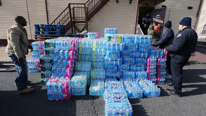 500 cases of water that the citizens of Plainfield, along with the Plainfield Firefighters, collected are taken from inside of Club Cosmo, 1209 South Second Street, Plainfield into a tractor trailer which is headed to the city of Flint, Michigan. The event that was held on Friday March 4, 2016  is in direct response to the tainted lead pipe water supply crisis in Flint Michigan. Here Plainfield Fire Department firefighters volunteer their time to get the water ready for shipment.