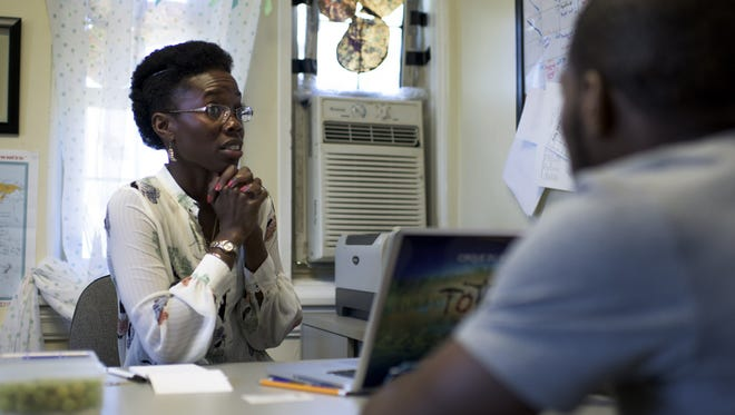Senior director of programming Vedra Chandler speaks with teen counselor Zhaire McCormick inside her office at the Neighborhood Center in Camden. Chandler returned to the city of her youth to work with the next generation.