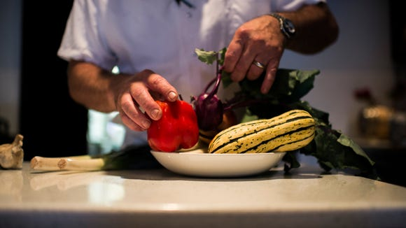 Chef and owner Todd Fuller organizes a bowl of fresh vegetables  at the Farm & Fisherman in Cherry Hill. Nose-to-tail ideals are not limited to meat, but also inspire cooking fruits, veggies and fish.