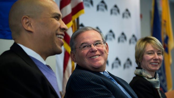 U.S. Senators Cory Booker, left, and Bob Menendez smile during an announcement of a major federal investment in the cityÕs efforts to transform and revitalize the Mt. Ephraim South neighborhood Tuesday, Dec. 13 in Camden.
