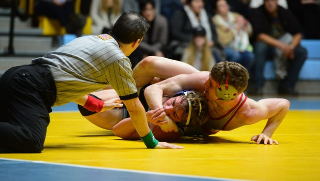 A wrestler pins his opponent during a match.