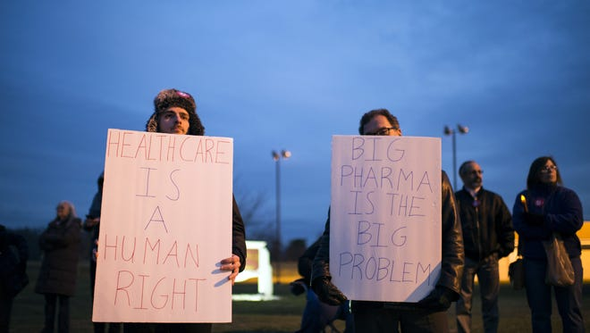 Kyle Moore, left, of Cinnaminson stands with fellow protesters advocating for health care in January in Marlton.