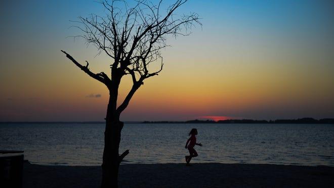 A little boy runs on the beaches of Assateague National Park at sunset. August 30, 2016.
