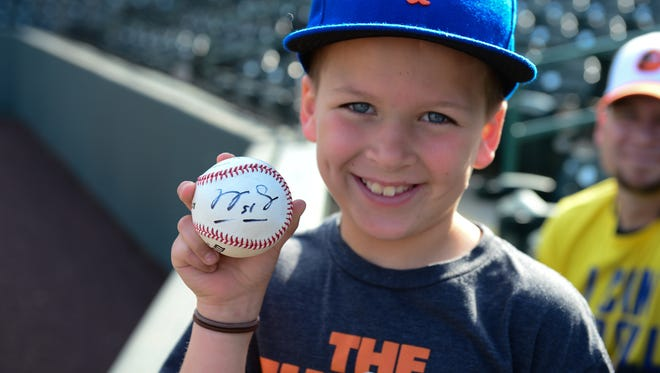 Tyler Hunt, 9, shows off his baseball autographed by Columbia Fireflies' Tim Tebow during batting practice at Perdue Stadium on Wednesday, May 10, 2017.