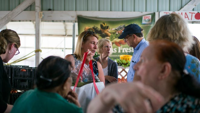 New Jersey Health Commissioner Cathy Bennett hands out bags of groceries during a WIC voucher program Thursday, Aug. 10, 2017 at Rottkamp Farms in Bridgeton.