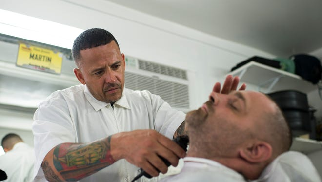 Martin Ortiz, 47, left, owner of Martin's Da Shop in Camden, trims the beard of long-time customer, Rich Treiber, in North Camden. Ortiz is in long-term recovery from addiction that included alcohol and opiates.