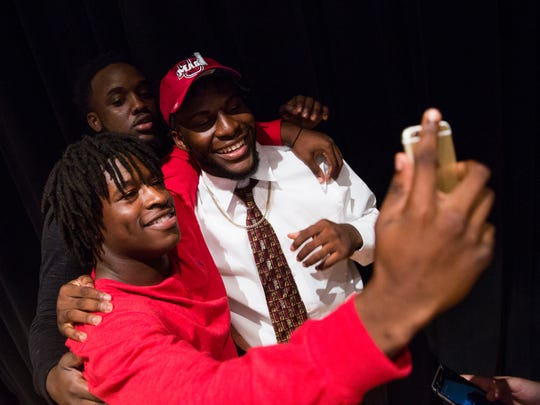 Claudin Cherelus takes a selfie with his teammates, Chauncy Pelissier, left, and Marvin Desir, after signing to play football with the University of Massachusetts Amherst during National Signing Day at Golden Gate High School on Wednesday, February 1, 2017 in Golden Gate.