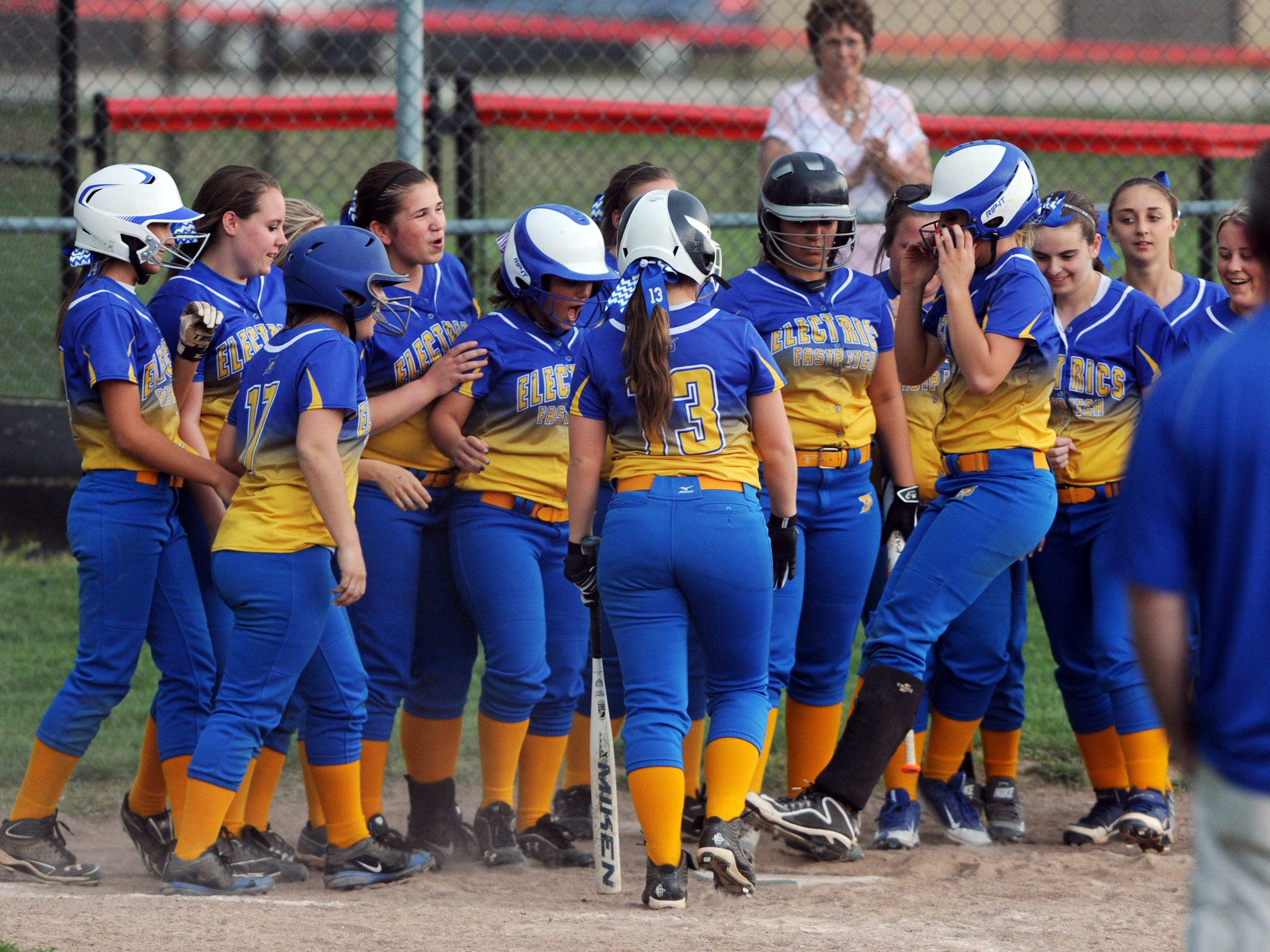 Philo's Mallory Hill is greeted by her teammates as she jumps on home plate after hitting a grand slam against Crooksville Monday night.