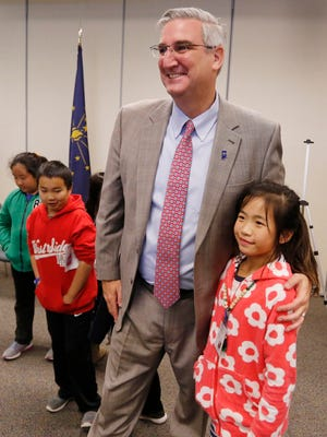 Gov. Eric Holcomb poses for a photogragh with Happy Hollow fifth grade student Kayla Xu Wednesday, November 8, 2017, at Ivy Tech Community College. Xu's wrote a paper as a second grade student at Cumberland Elementary School about the lack of a state insect. The paper was the initiative behind Cumberland Elementary's push to make the Say's firefly the Indiana state insect. Holcomb was at Ivy Tech Community College presenting his 2018 NextLevel Agenda, part of which is backing the Cumberland student's drive to name the Say's firefly the state insect.