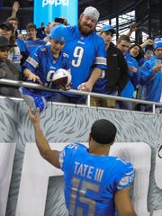Golden Tate gives his cleats to a Lions fan, as he leaves the field following the 2017 season finale at Ford Field.