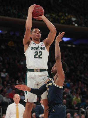 Michigan State's Miles Bridges scores against Michigan's Zavier Simpson during the first half of the Big Ten tournament semifinal March 3, 2018 at Madison Square Garden in New York.