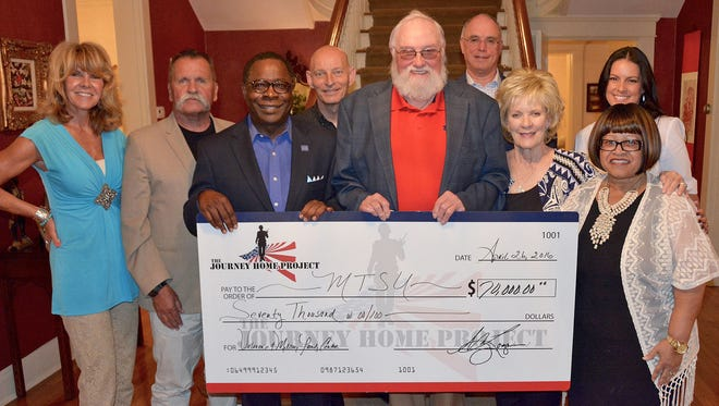 Charlie Daniels and his wife, Hazel, along with the directors of The Journey Home Project, present a $70,000 check to MTSU President Sidney A. McPhee to support the Veterans and Military Family Center after a dinner Tuesday evening at the President's Residence. The project has donated $120,000 to the center since it opened in November.