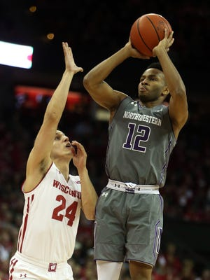 Northwestern Wildcats guard Isiah Brown (12) attempts a basket as Wisconsin Badgers guard Bronson Koenig (24) defends at the Kohl Center.