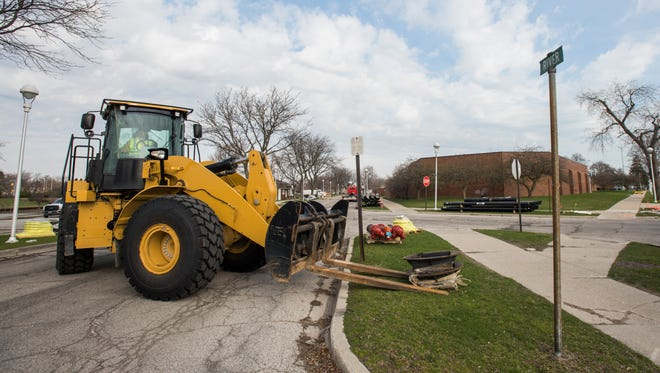 A front loader moves objects for road work Monday, April 9, along River Street between Glenwood Avenue and Stone Street  in Port Huron.