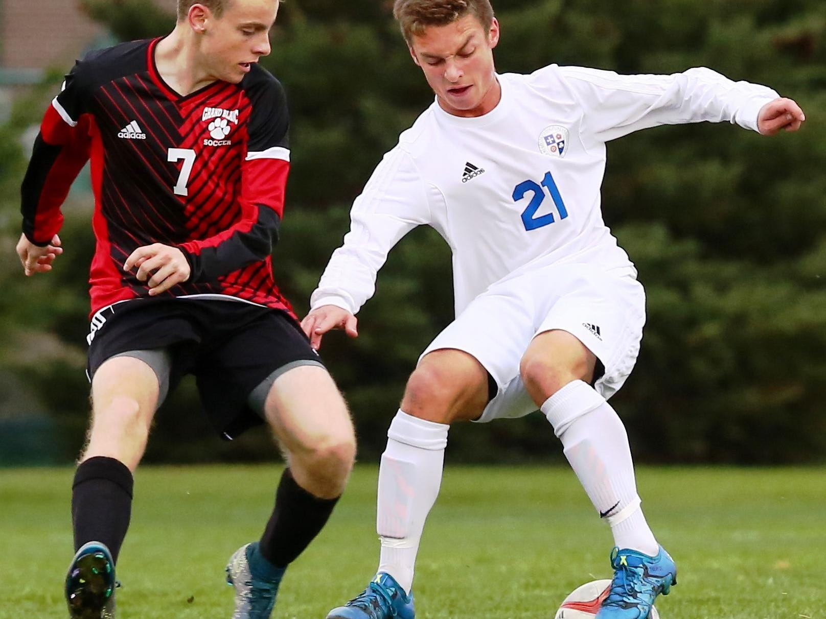 Catholic Central's Charles Trevisan (right) tries to keep control against Grand Blanc's Garrett Miler.