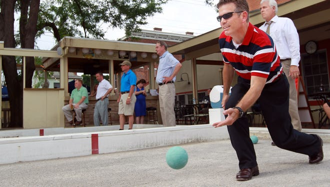 Fort Mitchell city administrator Chris Moriconi rolls a Bocce ball  at the Italianfest 2013 Mayor's Bocce Ball Tournament at Pompilios Restaurant, Newport. Behind him is Covington city manager Larry Klein.