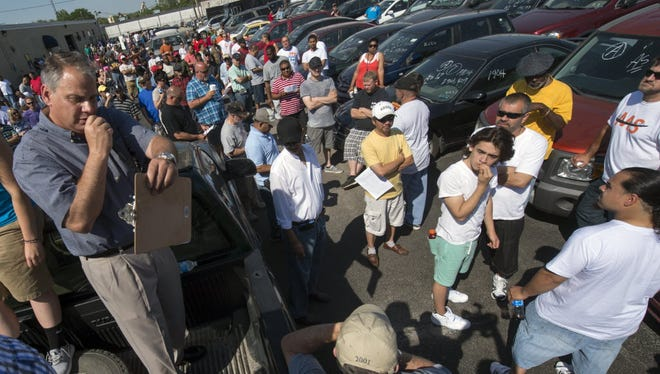 David P. Adcock, of Hellam Township, begins the auction from the back of a pickup truck during the York County Drug Task Force Auction May 25 in York. About 50 vehicles were auctioned off with other items. Most were seized during drug investigations.