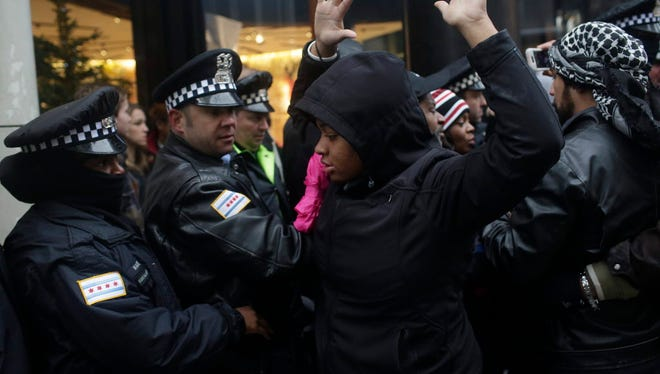 Police Officers watch as a demonstrator puts her hands up as she blocks the entrance to the Under Armour store as she protest the shooting of Laquan McDonald who was killed by a Chicago police Officer along Michigan Avenue also known as the Magnificent Mile November 27, 2015 in Chicago, Illinois. Chicago police Officer Jason Van Dyke was charged Tuesday with first degree murder for fatally shooting 17-year-old McDonald 16 times last year on the southwest side of Chicago after Van Dyke was responding to a call of a knife wielding man. The dash-cam video of Officer Van Dyke shooting McDonald was released by the Chicago Police department earlier this week after a judge denied Van Dyke bail during his bond hearing at Leighton Criminal Court.