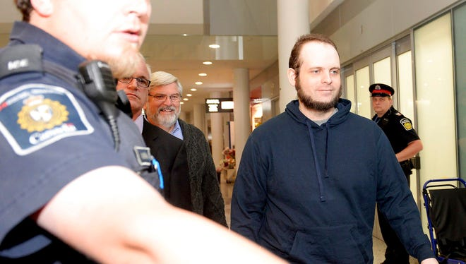 Joshua Boyle is escorted by authorities to a media availability at Toronto's Pearson International Airport on Friday, Oct. 13, 2017. Boyle, his wife Caitlin Coleman, and their three children landed in Canada after they were kidnapped in Afghanistan while on a backpacking trip and held hostage for five years by the Taliban-linked Haqqani network.