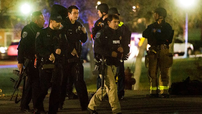 Police officers search for a gunman near Red Butte Garden on the University of Utah campus in Salt Lake City, Monday, Oct. 30, 2017. Police say a deadly shooting occurred near the school campus on Monday. (Rick Egan/The Salt Lake Tribune via AP)