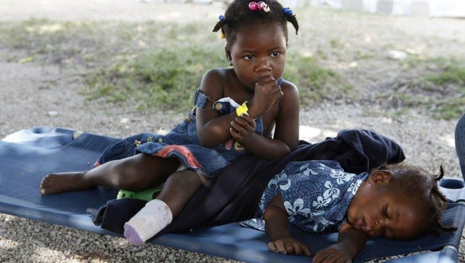 Shakira Thomas, 3, sits with her brother, Thomas Johnson, 1, in World Harvest Mission of Lake Worth, Fla. Cinder blocks fell on her during the quake, forcing doctors to amputate her foot.