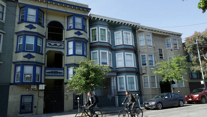 Bicyclists ride past a multi-unit property, at center, where a woman was charged with murder in the slaying of her roommate in San Francisco, Thursday, June 7, 2018. A dismembered body was discovered in oozing plastic bags inside a maggot-filled storage container at their home, prosecutors said Wednesday.