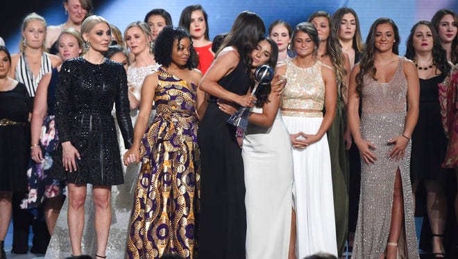 Jennifer Garner, front, embraces gymnast Aly Raisman after presenting the Arthur Ashe Award for Courage, at the ESPY Awards at Microsoft Theater on Wednesday, July 18, 2018, in Los Angeles. Holding hands in front left are former gymnast Sarah Klein and former Michigan State softball player Tiffany Thomas Lopez. More than 140 survivors of sexual abuse by a former team doctor for USA Gymnastics and Michigan State University joined hands on stage to be honored with the award. (Photo by Phil McCarten/Invision/AP)