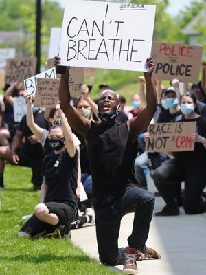 Gregory King, a dance professor at Kent State, kneels during a Black Lives Matter protest Tuesday in Kent, held in response to the recent death of George Floyd, a black man who was killed by police in Minnesota.