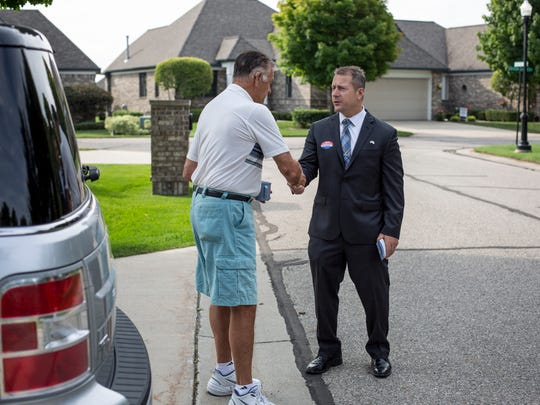 David VanAssche, right, shakes hands with Bill Heine while walking door-to-door to promote his campaign Thursday, July 28, 2016 in Edison Shores in Port Huron. VanAssche, a republican,  is running for Congress in Michigan's 10th Congressional District.