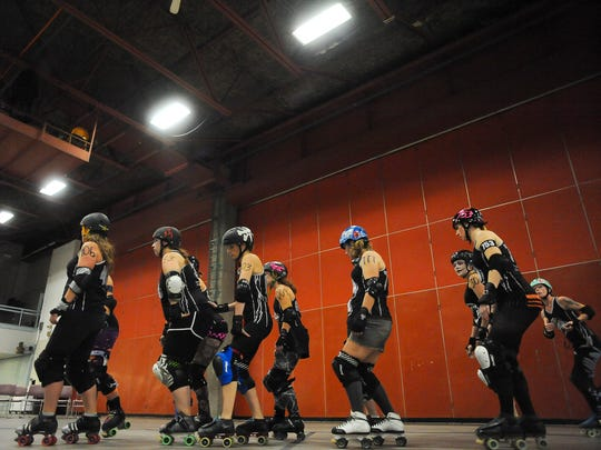 The Electric City Roller GrrrlZ warm up before a bout at the Four Seasons Arena.