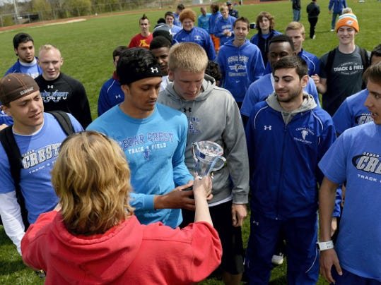 Joan-Marie Norman, presents the Lebanon County Track and Field Championship trophy to Landy Cruz after he and his Cedar Crest  teammates won their 18th straight county meet at Lebanon High School on Saturday.