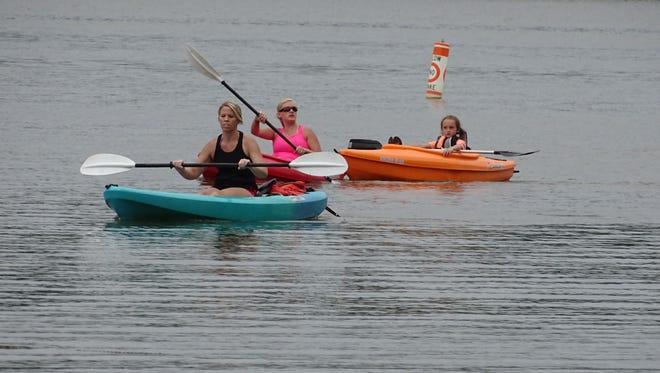 Women kayak Thursday afternoon toward the beach at Charles Mill Lake Park.