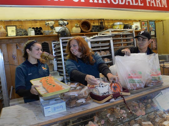 Springdale Farm employees Alexa Caputo, 14, of Cherry Hill, her mother Jackie Caputo, and baker Jonathan Salto (from left), with some of the Springdale Farm bakery's seasonal offerings.