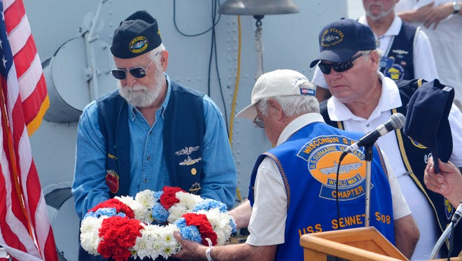 Members of the Wisconsin Submarine Veterans Base lower a wreath into the Manitowoc River in memory of fallen members of the U.S. military on Sunday. The wreath placing was one of the final parts of a Tolling of the Boats ceremony on the final day of Subfest in Manitowoc.