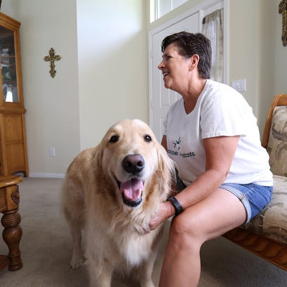 Lori Eagen with her service dog, Tober, in their home in Kissimmee, Fla. The golden retriever can tell when Lori is about to have a seizure, find her family members and alert them.