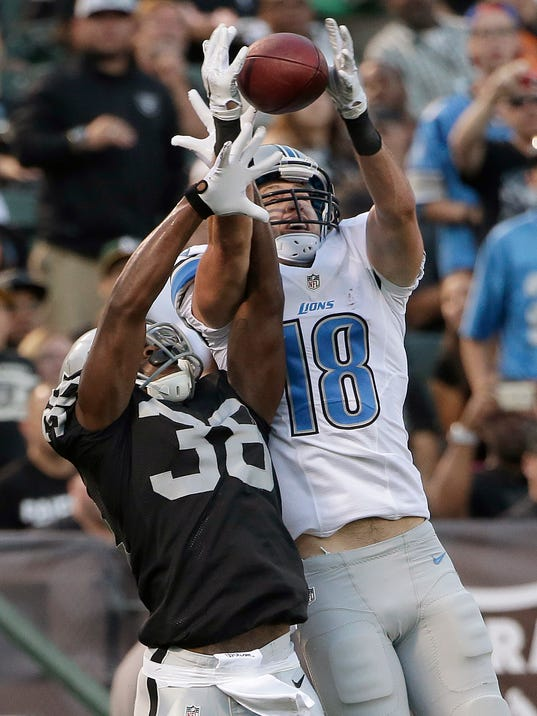 Detroit Lions wide receiver Kris Durham (18) catches a 4-yard touchdown pass over Oakland Raiders cornerback T.J. Carrie (38) during the first quarter of an NFL preseason football game in Oakland, Calif., Friday, Aug. 15, 2014. (AP Photo/Marcio Jose Sanchez)